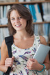 Female student against bookshelf with tablet PC and bag in libra