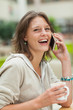 Cheerful woman using mobile phone while drinking coffee
