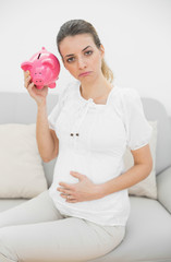 Unhappy pregnant woman shaking a piggy bank while touching her b