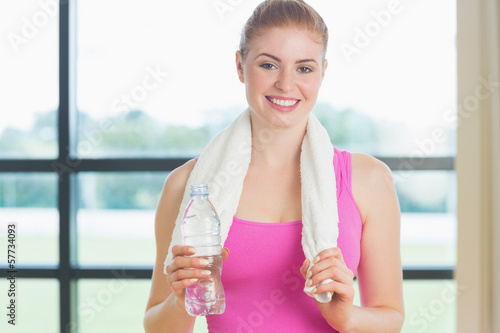 Portrait of a woman with towel around neck holding water bottle