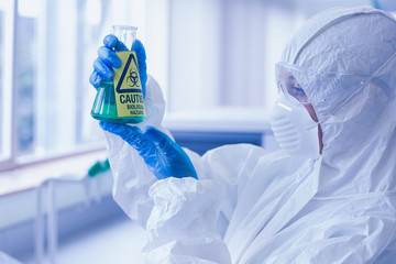 Scientist in protective suit with hazardous chemical in flask at