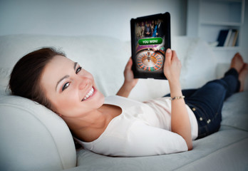 Happy woman lying on couch and gambling on tablet