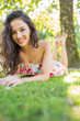 Stylish cheerful brunette lying on a lawn looking at camera