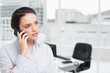 Serious elegant businesswoman using cellphone in office