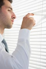 Attractive stern businessman spying through roller blind