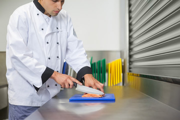 Chef cutting raw salmon with knife on blue cutting board