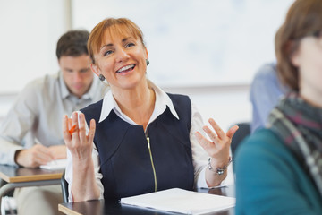 Laughing female mature woman sitting in classroom