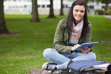 Happy brunette student using tablet sitting on bench