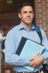 Attractive mature student posing in corridor holding some files