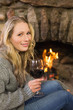 Beautiful woman with wineglass in front of lit fireplace