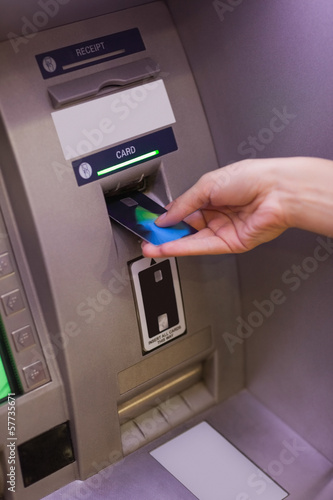 Close up of hand pulling in debit card