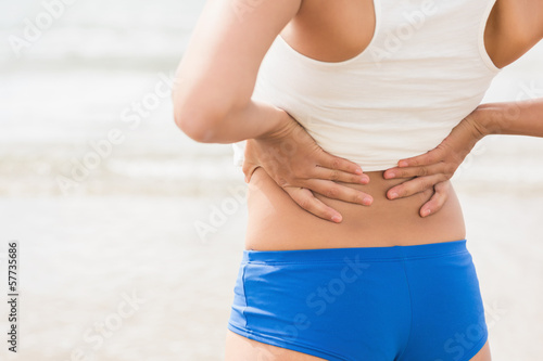 Mid section of sporty woman holding her back