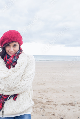 Cute smiling woman in stylish warm clothing on beach