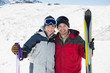 Portrait of a smiling couple with ski equipment on snow