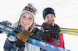 Close-up of a smiling couple with ski boards on snow