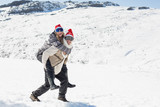Full length of a man piggybacking cheerful woman on snow