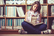 Female student against bookshelf reading a book on the library f