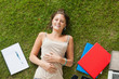 Smiling young woman lying on grass with books