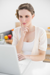 Attractive calm woman sitting thoughtful in front of her laptop