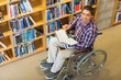 Man in wheelchair by bookshelf in the library