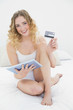 Pretty smiling blonde sitting on bed holding tablet and credit c