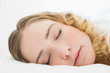 Pretty content blonde lying in bed resting with closed eyes