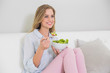 Happy casual blonde sitting on couch holding salad bowl