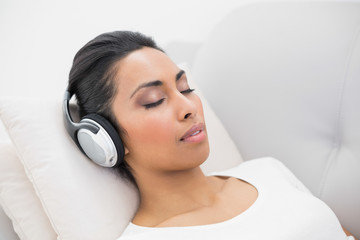 Lovely relaxing woman listening to music while lying on couch