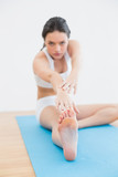 Blurred toned woman doing the hamstring stretch on exercise mat poster