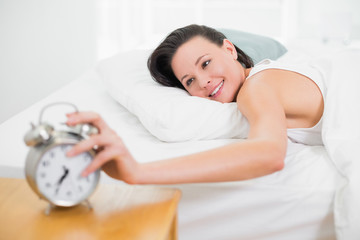 Smiling woman in bed extending hand to alarm clock