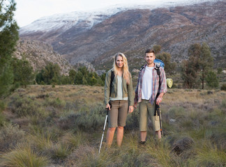 Couple with backpacks and trekking poles against mountain