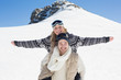 Wan piggybacking cheerful woman against snow covered hill