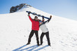 Full length of a cheerful couple with ski board on snow