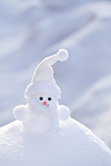 Little white snowman on the snowbank.