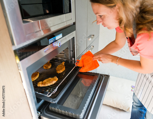 beautiful woman gets out meat of the oven