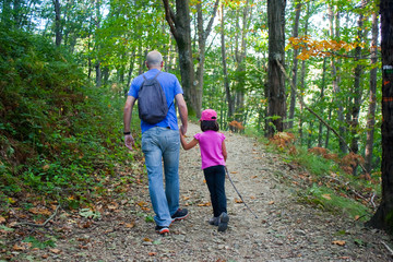 Father and daughter walking in the forest