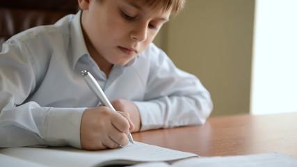 Child writes homework. Dolly shot
