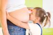 Little girl kissing pregnant mother