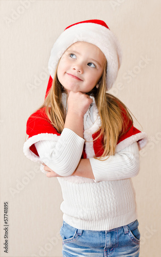 Happy smiling little girl in christmas hat is dreaming