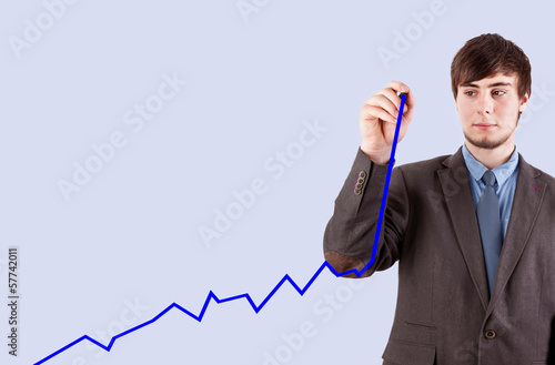 Young business man drawing chart on the blackboard