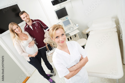 Doctor And Expectant Couple In Examination Room
