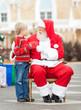 Boy Giving Wish List To Santa Claus
