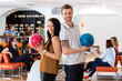 Friends Standing Together With Bowling Balls in Club