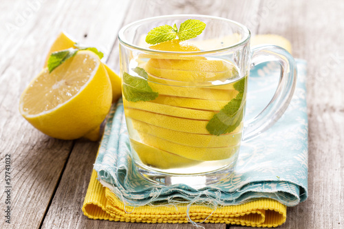 Tea with mint and whole lemon in a transparent cup