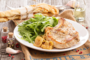Roasted pork with apples and onions served with fresh arugula