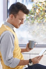Young man reading news drinking coffee