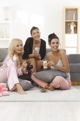 Friends watching tv in pyjamas