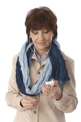 Mature woman using mp3 player