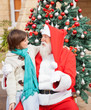 Boy Looking At Santa Claus In Front Of Christmas Tree