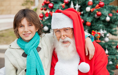 Boy With Arm Around Santa Claus Outdoors